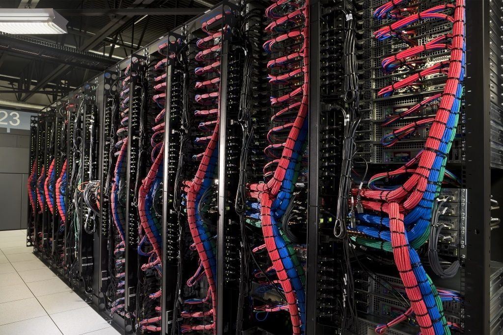 Very large amount of color coded cables on back of row of network servers